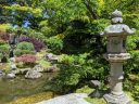 Tall stone lantern in foreground with colorful plants, pond, large stones, and waterfall in background, Japanese Tea Garden, Golden Gate Park, San Francisco, California